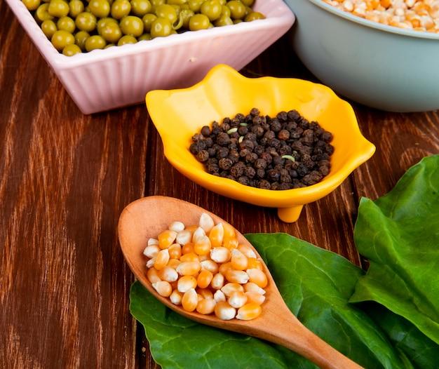 Close-up beeld van maïs zaden in houten lepel en kom van zwarte peper met spinazie op houten tafel