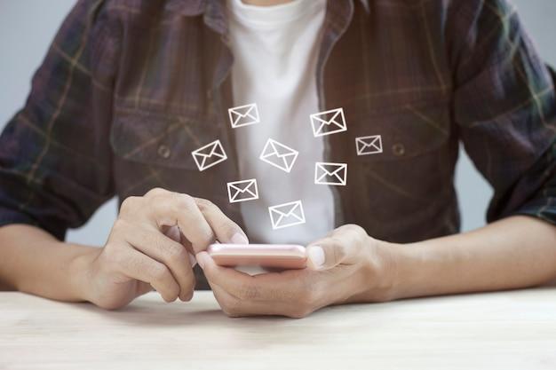 Close-up beeld van man met behulp van digitale mobiele telefoon met e-mailpictogram op houten tafel