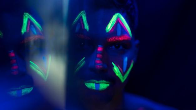 Close-up beeld van man met kleurrijke fluorescerende make-up