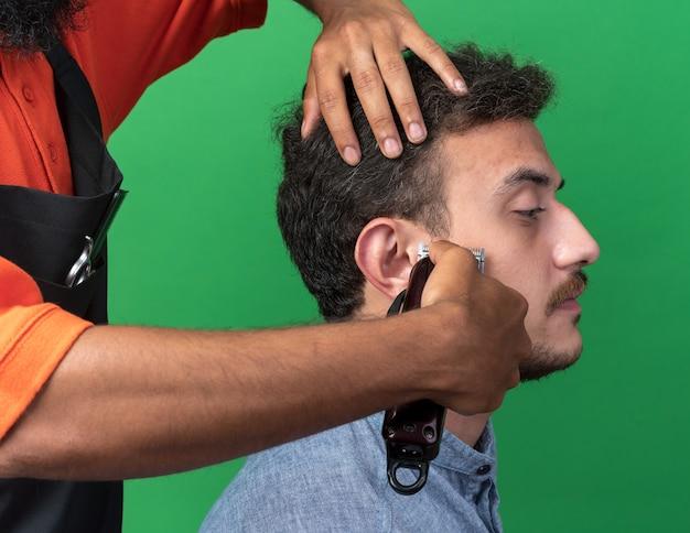 Close-up beeld van mannelijke kapper handen trimmen gezicht van zijn jonge cliënt