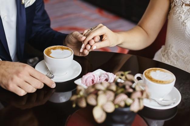 Close-up beeld van mannenhand met vrouwelijke hand met dure trouwring