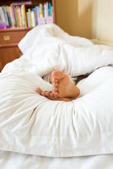 Close-up beeld van meisjes voeten liggend op wit kussen in de slaapkamer