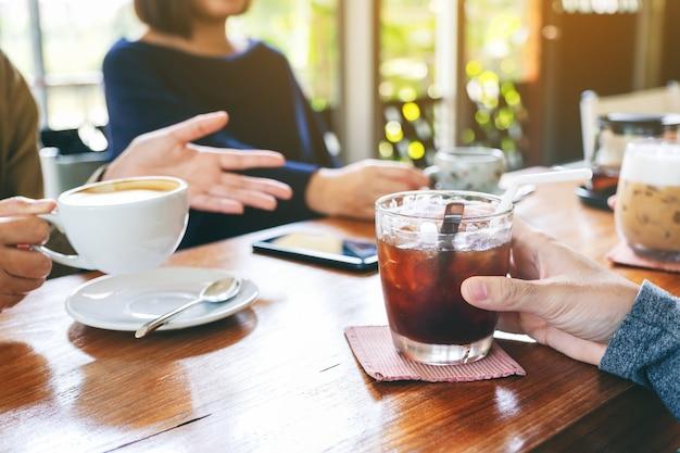 Close-up beeld van mensen die genoten hebben van praten en samen koffie drinken in café