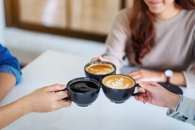 Close-up beeld van mensen die genoten van het drinken en rammelen van koffiekopjes samen op tafel in café