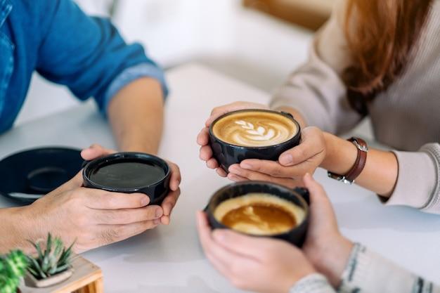 Close-up beeld van mensen die koffie vasthouden en ervan genoten om koffie te drinken op tafel in café