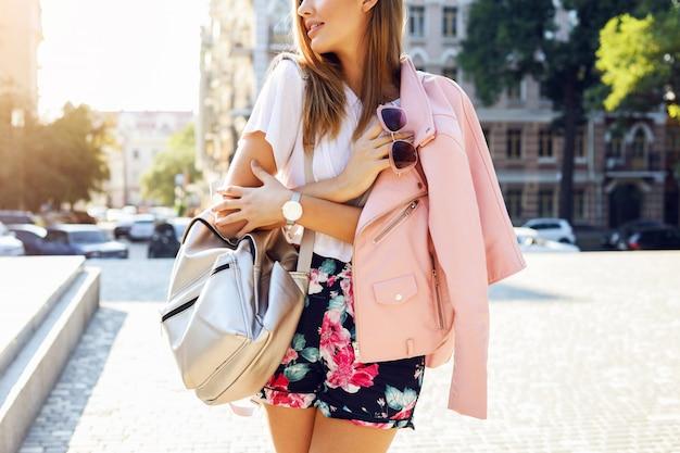Close-up beeld van mode details, roze jas, stijlvolle shorts, zonnebril bij de hand, trendy tas. vrij stijlvolle vrouw in herfst casual outfit wandelen in de stad. street style.