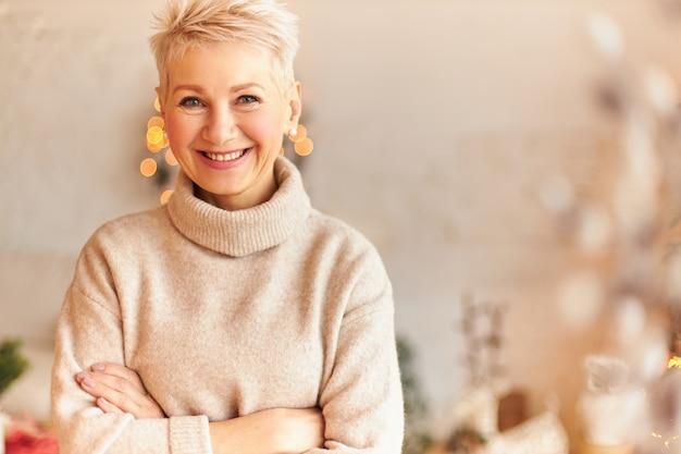 Close-up beeld van modieuze dolblij europese vrouw van middelbare leeftijd in coltrui kasjmier trui armen gekruist en glimlachend vol vertrouwen, familie wachten op feestelijk diner op kerstavond
