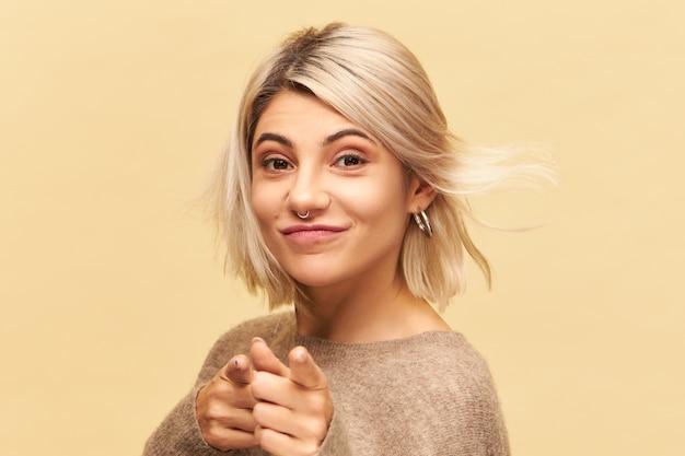 Close-up beeld van mooi mooi meisje met slordig blond haar en neusring glimlachend en wijsvinger, uitdaging voor u gooien. lichaamstaal, tekens, symbool en gebaarconcept