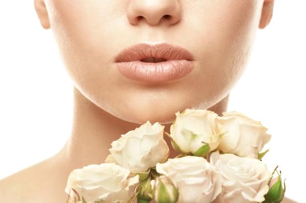 Close-up beeld van mooie jonge vrouw met natuurlijke lippen make-up en bloemen op witte ondergrond