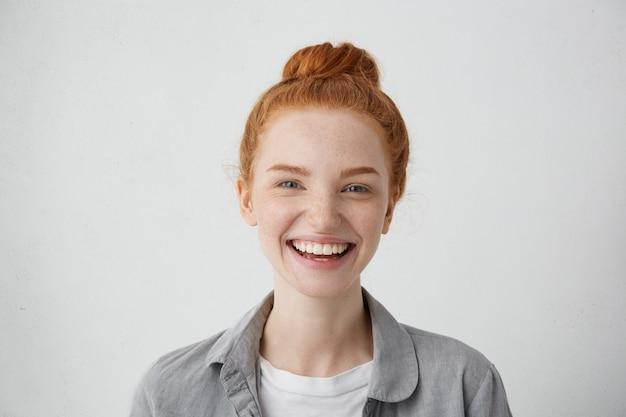 Close-up beeld van mooie vrouw met rood haar knoop, blauwe charmante ogen, sproeten en zachte glimlach met heerlijke uitdrukking