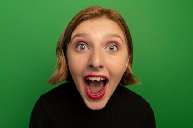 Close-up beeld van onder de indruk jong blond meisje geïsoleerd op groene muur