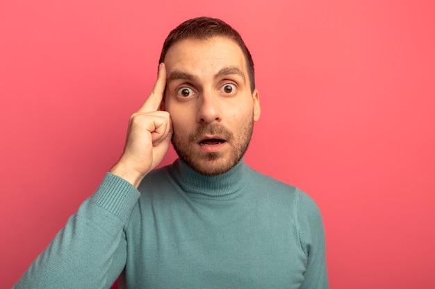 Close-up beeld van onder de indruk jonge blanke man doet denk gebaar geïsoleerd op karmozijnrode muur met kopie ruimte