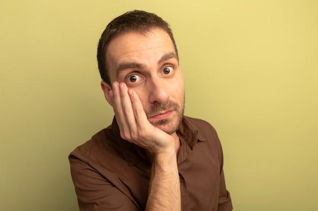 Close-up beeld van onder de indruk jonge blanke man hand zetten gezicht kijken camera geïsoleerd op olijfgroene achtergrond met kopie ruimte