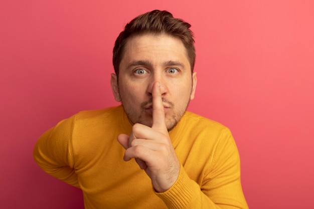 Close-up beeld van onder de indruk jonge blonde knappe man die stilte gebaar doet en hand achter de rug houdt