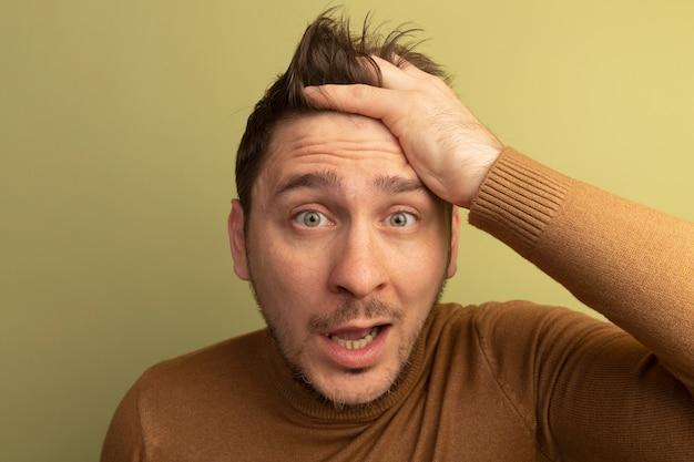 Close-up beeld van onder de indruk jonge blonde knappe man hand op het hoofd zetten