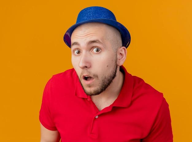 Close-up beeld van onder de indruk jonge knappe feest man met feestmuts kijken naar voorzijde geïsoleerd op oranje muur