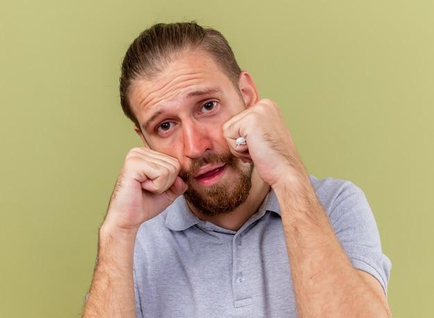 Close-up beeld van onder de indruk jonge knappe slavische zieke man die een servet hoding met vuisten op gezicht geïsoleerd op olijfgroene muur
