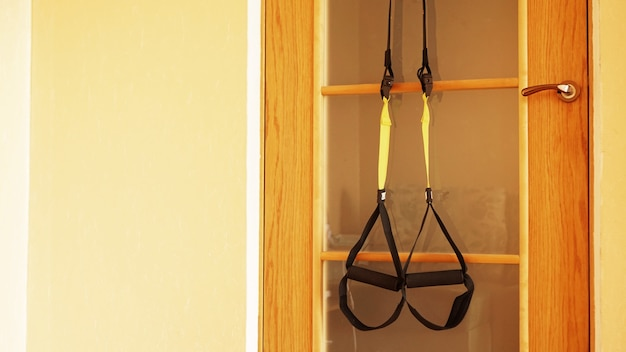 Close-up beeld van ophanging op deur op houten achtergrond training thuis - fitness thuis