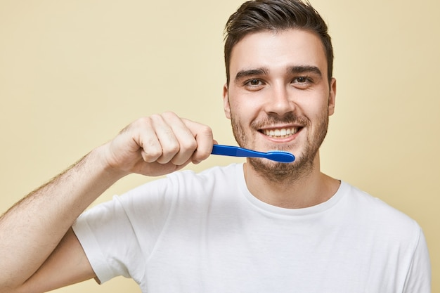 Close-up beeld van positieve jonge ongeschoren man die plastic tandenborstel vasthoudt tijdens het poetsen van tanden in de badkamer voor de spiegel, het verzorgen van mondhygiëne, met tevreden gelaatsuitdrukking