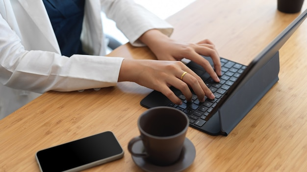 Close-up beeld van professionele zakenvrouw tablet toetsenbord te typen tijdens het werken aan haar project