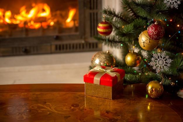 Close-up beeld van rode geschenkdoos op houten tafel voor brandende open haard en kerstboom. lege plaats voor tekst
