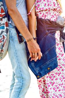 Close-up beeld van romantische zoete paar verliefd, hand in hand, zonsondergang heldere kleuren, stijlvolle outfits.
