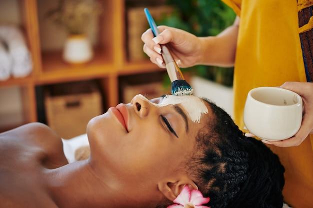 Close-up beeld van schoonheidsspecialiste zuiverende en minimaliseren poriën klei masker toe te passen op het gezicht van mooie jonge zwarte vrouw