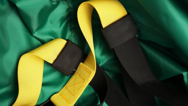 Close-up beeld van schorsing op groene achtergrond training thuis - fitness thuis