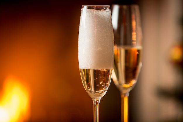 Close-up beeld van schuim in glazen gevuld met champagne met brandende open haard op de achtergrond