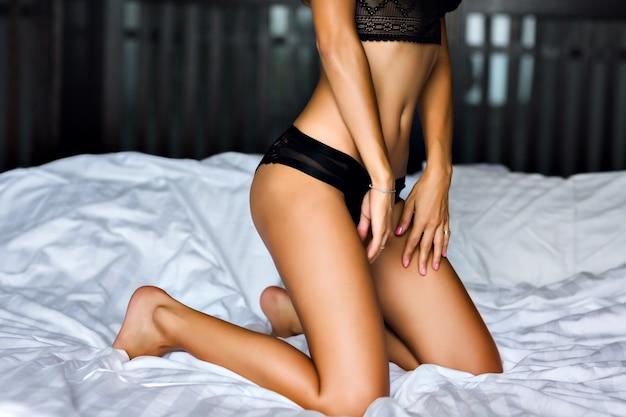 Close-up beeld van sexy vrouw die zich voordeed op het bed, slank gebruinde lichaam, zwarte lingerie, geniet van haar ochtend, luxe levensstijl.