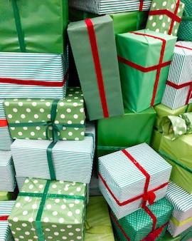 Close-up beeld van stapel van veel kerstcadeaus. stapel groene dozen met rode linten met nieuwjaarscadeautjes