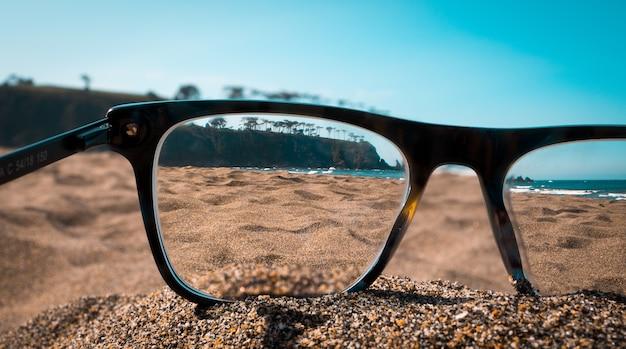 Close-up beeld van strand gezien vanuit de lenzen van zwarte bril