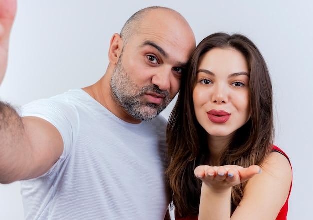 Close-up beeld van tevreden volwassen paar man hand uitstrekken naar en vrouw klap kus verzenden