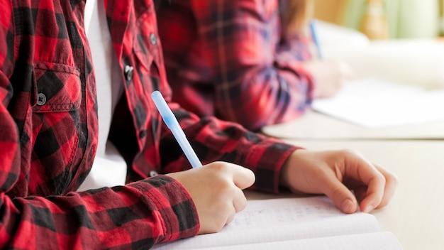 Close-up beeld van tienermeisje dat pen vasthoudt en schrijft terwijl ze huiswerk op school doet.