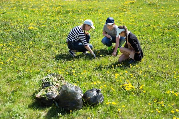Close-up beeld van tieners met handschoenen en vuilniszakken lopen. ecologie bescherming concept.