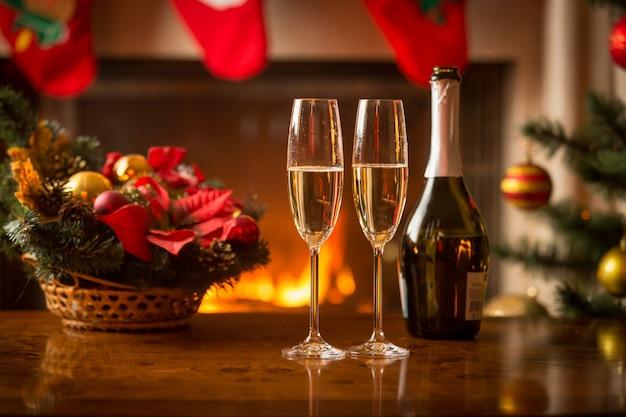 Close-up beeld van twee glazen champagne op kersttafel naast brandende open haard