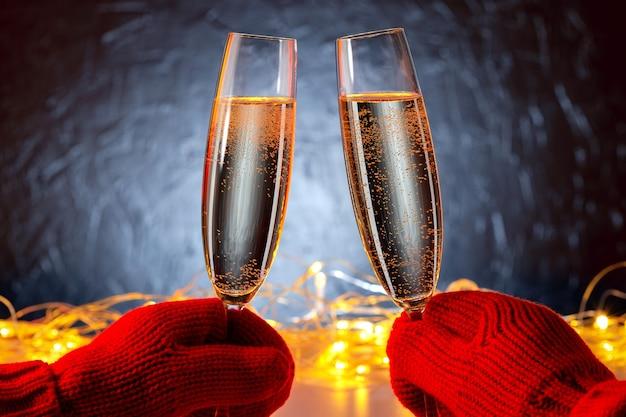 Close-up beeld van twee handen dragen warme outfit bedrijf in handen glazen mousserende wijn