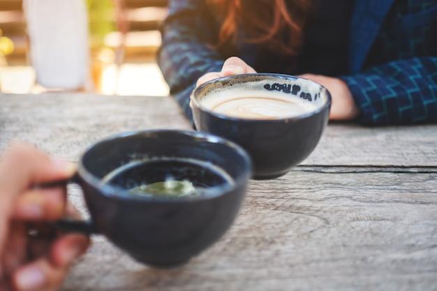 Close-up beeld van twee mensen rammelende koffiemokken op houten tafel