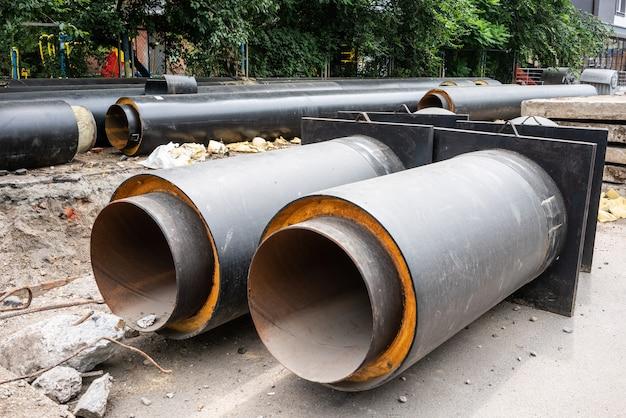 Close-up beeld van twee nieuwe geïsoleerde waterleidingen op de weg van de stad in zomerdag