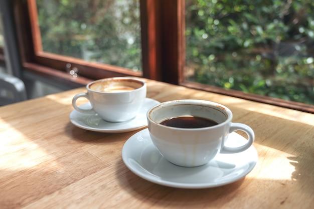 Close-up beeld van twee witte kopjes warme koffie op houten tafel in café