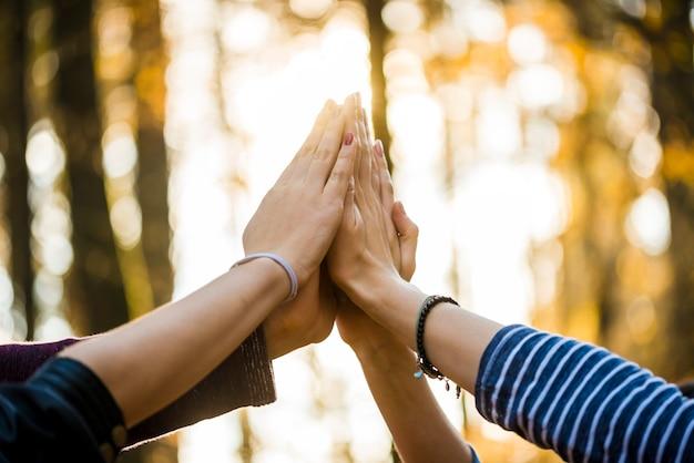 Close-up beeld van vier mensen samen met hun handen hoog omhoog in de lucht