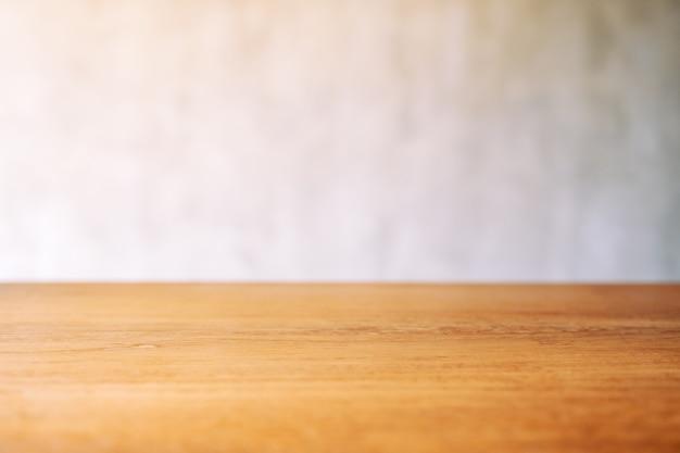 Close-up beeld van vintage houten tafel met wazig betonnen muur achtergrond