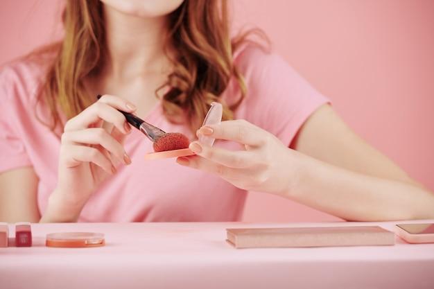 Close-up beeld van vrouw die roze compacte blos aanbrengt met synthetische brush