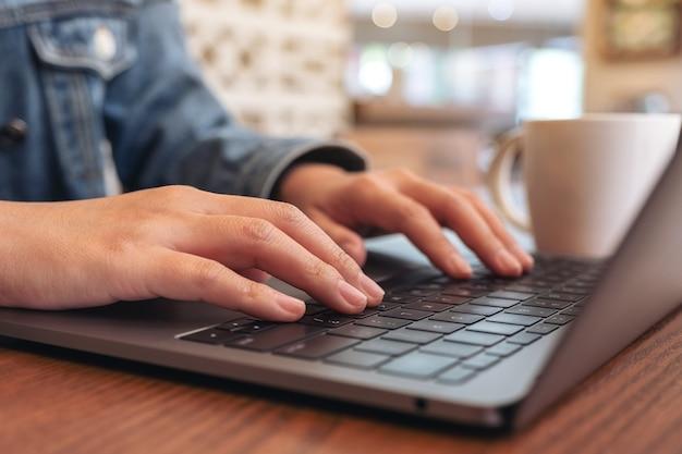Close-up beeld van vrouw handen gebruiken en typen op laptop computertoetsenbord met koffiekopje op tafel