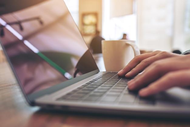 Close-up beeld van vrouw handen met behulp van en typen op laptop toetsenbord op tafel