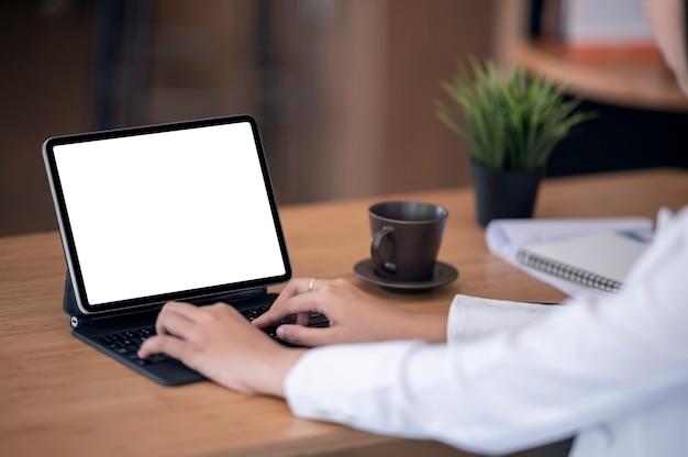 Close-up beeld van vrouw handen typen op tablet toetsenbord met leeg scherm zittend aan houten tafel.