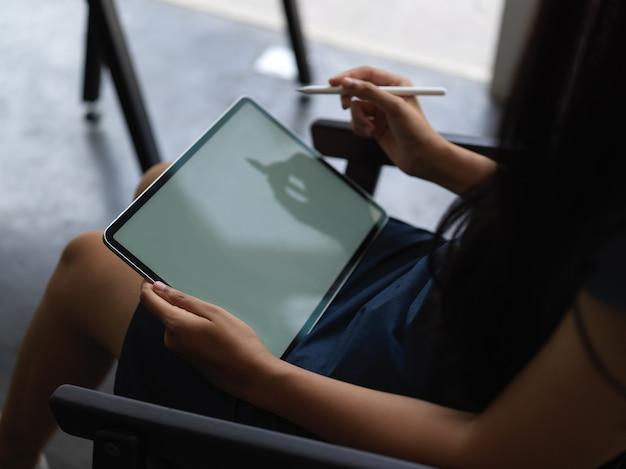 Close-up beeld van vrouw met behulp van mock-up tablet zittend op een stoel op haar werkruimte