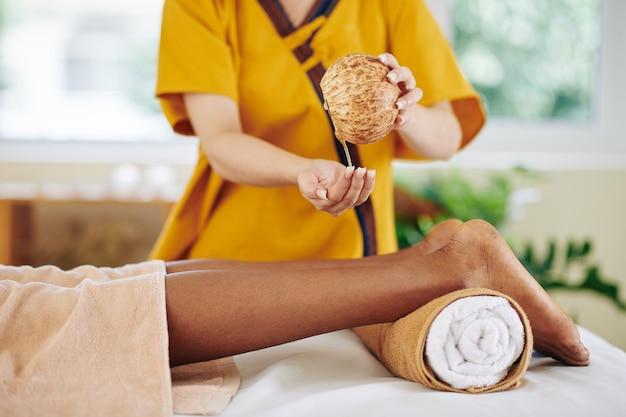 Close-up beeld van vrouw schoonheidsspecialiste kokosolie in de hand gieten om het op te warmen voordat kalveren van jonge zwarte vrouw masseren