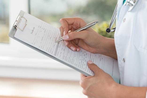Close-up beeld van vrouwelijke arts handen patiënt registratieformulier invullen. gezondheidszorg en medisch concept