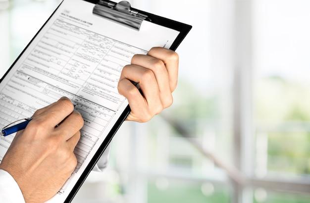 Close-up beeld van vrouwelijke arts handen vullen patiënt registratieformulier